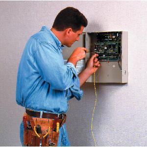 Installer fitting a Honeywell alarm system.